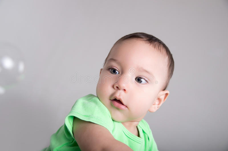 Leuke babyjongen die en pret met bellen spelen hebben stock foto