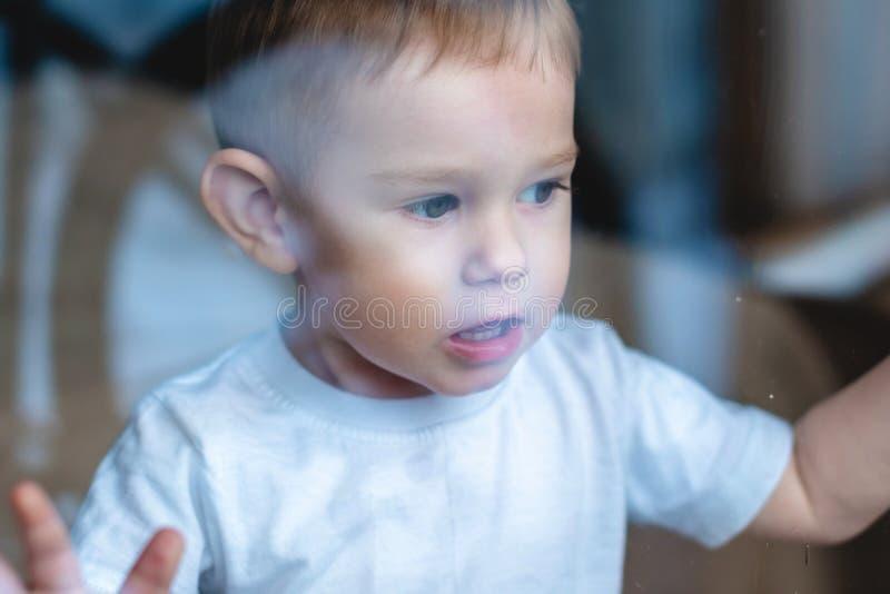 Leuke babyjongen die in het glazen venster kijken Eenzaamheid van kinderen en het wachten op vriendelijkheid Weeshuis en wezen stock foto's