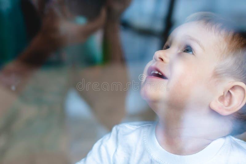 Leuke babyjongen die in het glazen venster kijken Eenzaamheid van kinderen en het wachten op vriendelijkheid Weeshuis en wezen royalty-vrije stock foto's