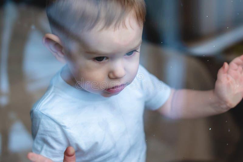 Leuke babyjongen die in het glazen venster kijken Eenzaamheid van kinderen en het wachten op vriendelijkheid Weeshuis en wezen royalty-vrije stock foto