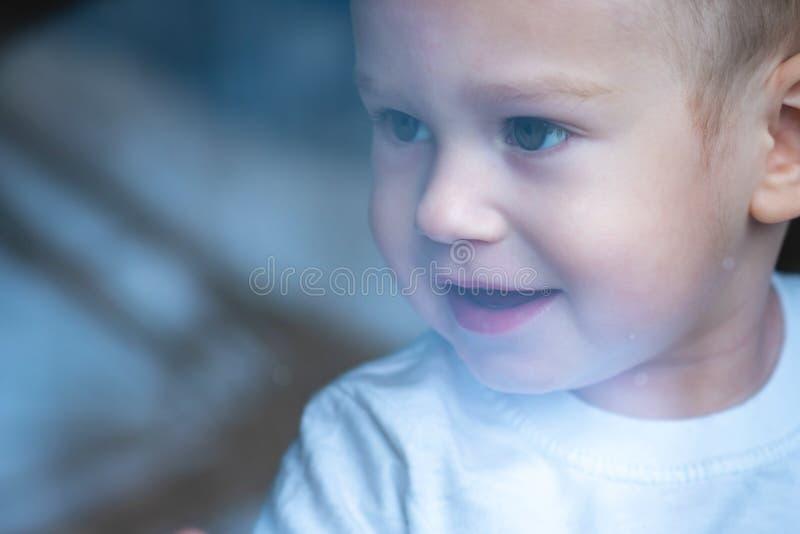 Leuke babyjongen die in het glazen venster met bezinning kijken Eenzaamheid van kinderen Weeshuis en wezen royalty-vrije stock fotografie
