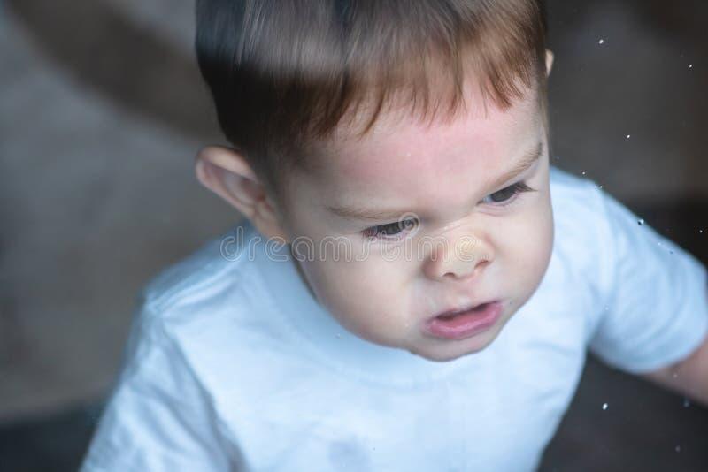 Leuke babyjongen die in het glazen venster met bezinning kijken Eenzaamheid van kinderen Weeshuis en wezen royalty-vrije stock afbeeldingen