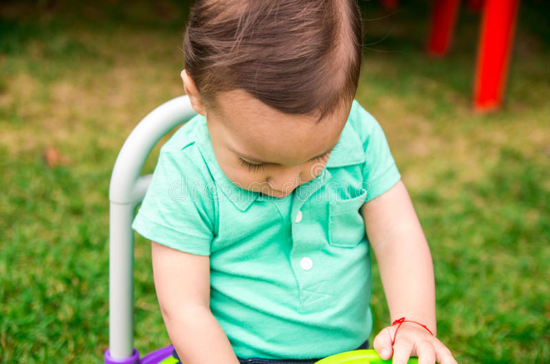 Leuke babyjongen die turkooise t-shirt en gekamd haar dragen, die buiten op grasrijke oppervlakte zitten die rond spelen stock afbeeldingen