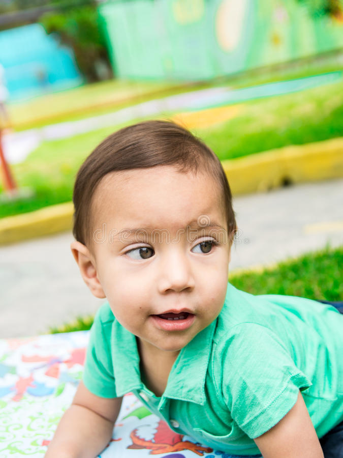 Leuke babyjongen die turkooise t-shirt en gekamd haar dragen, die buiten op grasrijke oppervlakte zitten die rond spelen royalty-vrije stock afbeelding