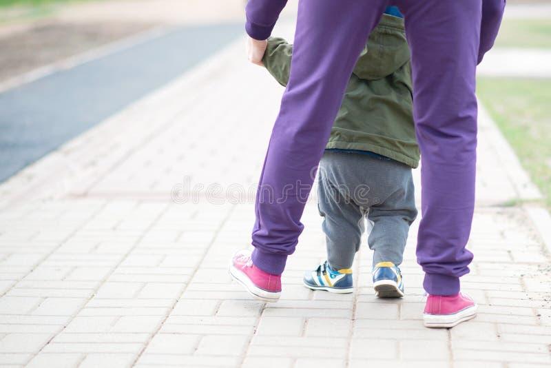 Leuke babyjongen die zijn eerste stappen leren te lopen en te maken het mamma houdt zijn hand de voeten van het kind sluiten omho stock foto's