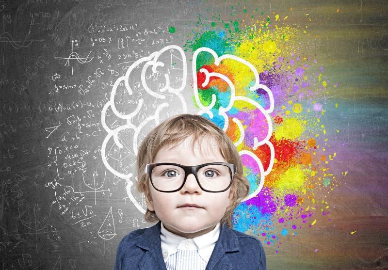 Leuke babyjongen in glazen en kleurrijke hersenenschets stock foto