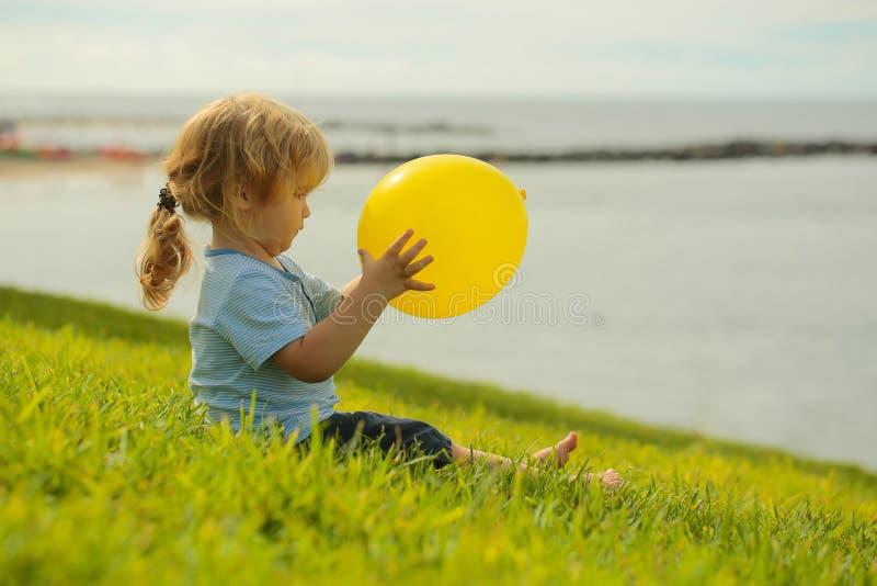Leuke babyjongen met gele stuk speelgoed ballon royalty-vrije stock foto's