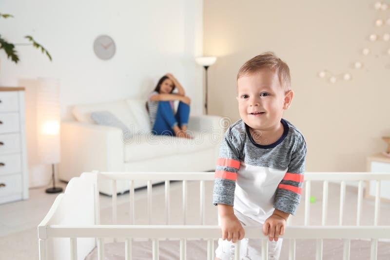 Leuke babyjongen in voederbak en jonge moeder stock foto's