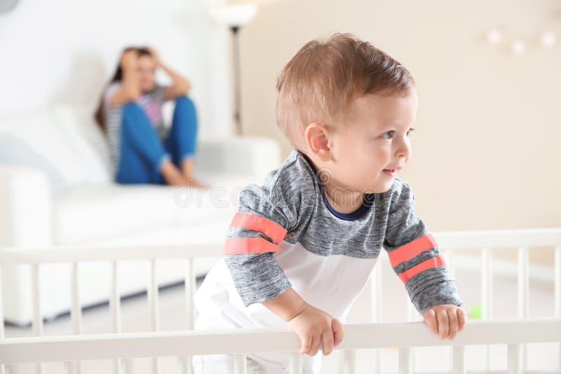 Leuke babyjongen in voederbak en jonge moeder royalty-vrije stock afbeelding