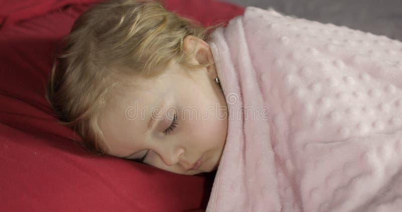 Leuke babyslaap op het bed thuis Meisjeslaap in ochtendlicht stock foto
