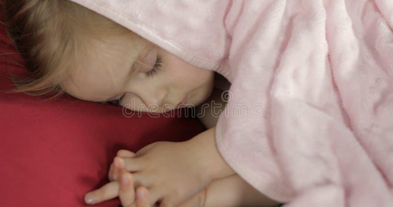 Leuke babyslaap op het bed thuis Meisjeslaap in ochtendlicht stock fotografie