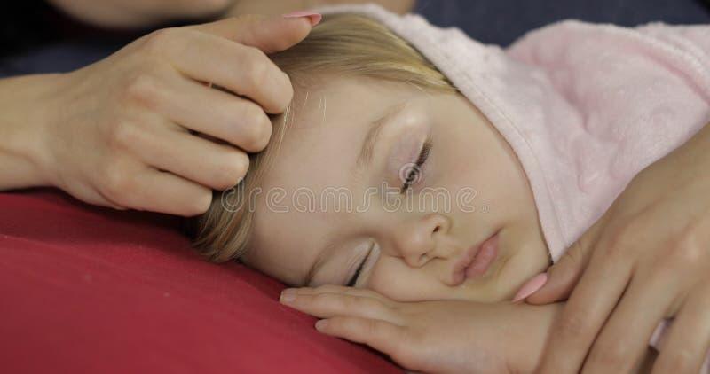 Leuke babyslaap op het bed thuis Meisjeslaap in ochtendlicht stock afbeelding
