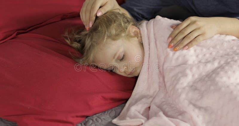 Leuke babyslaap op het bed thuis Meisjeslaap in ochtendlicht stock afbeeldingen