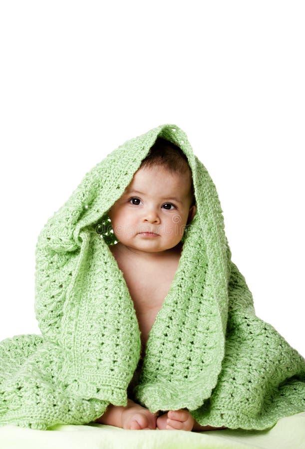 Leuke babyzitting tussen groene deken. stock afbeelding