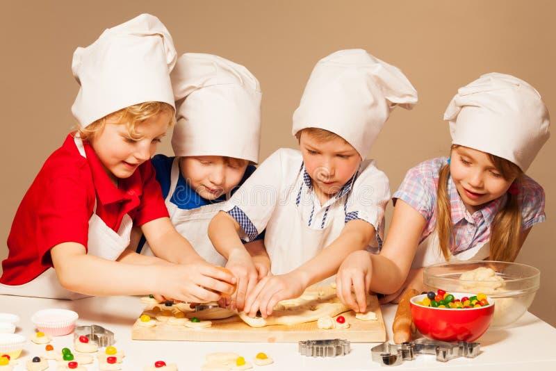 Leuke bakkers die pret hebben die suikergoed gevulde koekjes maken stock foto's