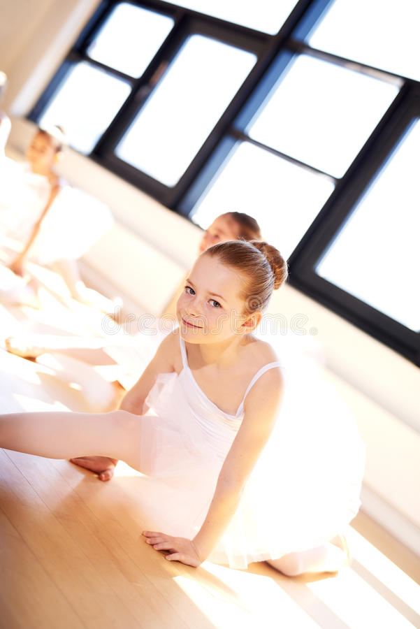 Leuke Ballerina die haar Benen op de Vloer verdelen stock foto