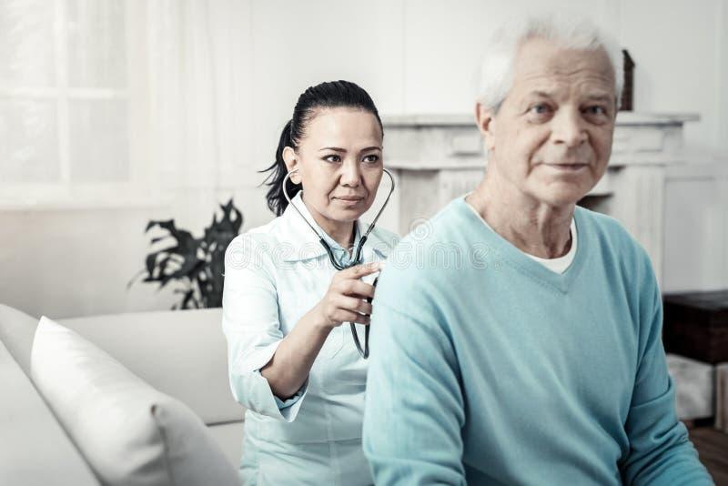 Leuke betrouwbare verpleegster die en aan het patiëntenlichaam zitten luisteren royalty-vrije stock foto's