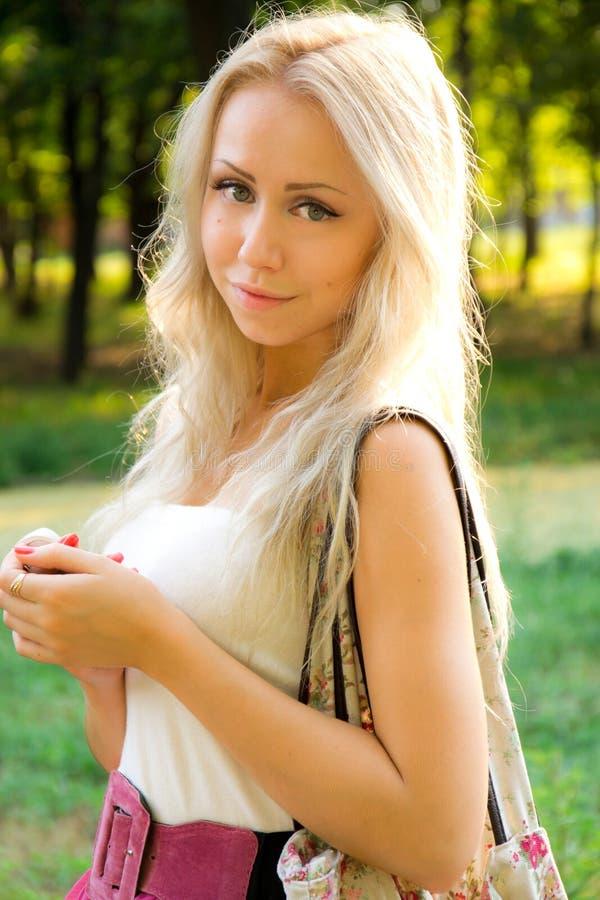 Leuke blond op aard in het park stock fotografie