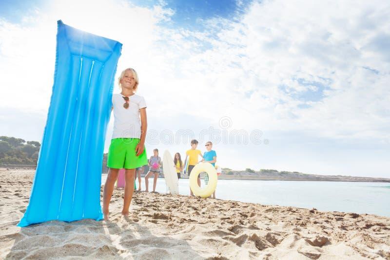 Leuke blonde glimlachende jongen met matrass op zandig strand royalty-vrije stock foto's