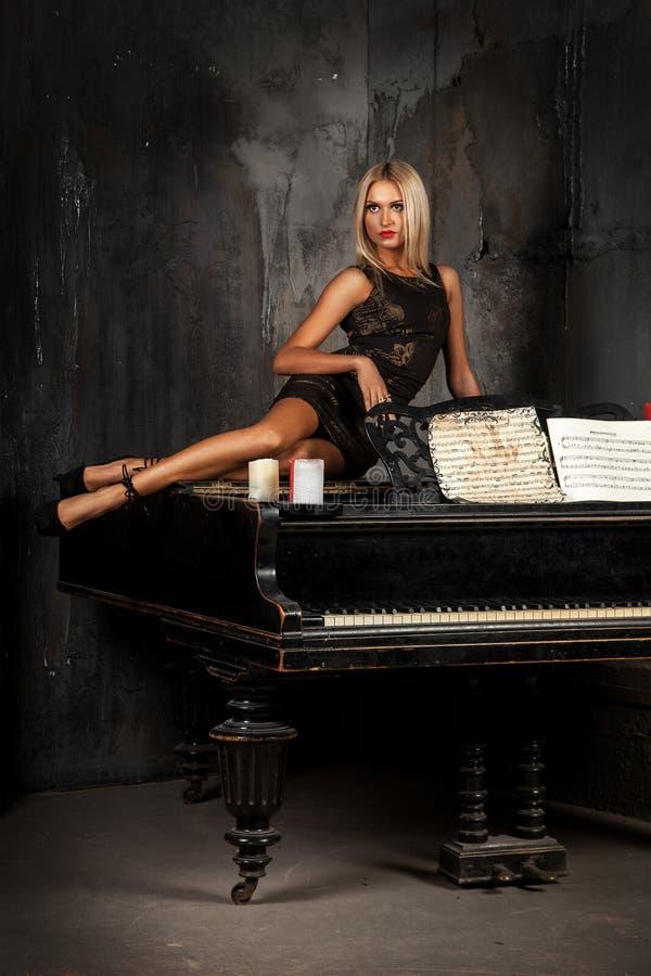 Leuke blonde op piano liggen en haarvrouw die weg kijken stock foto's