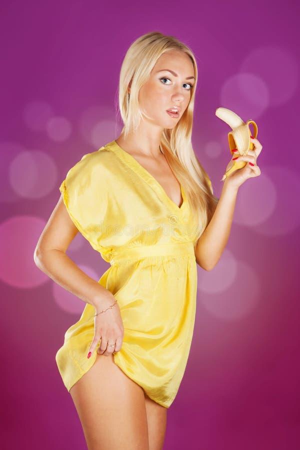 Leuke blonde vrouw die een banaan klaar houden te eten royalty-vrije stock foto