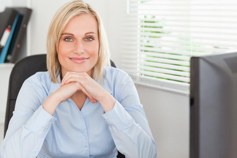 Leuke blonde vrouw met kin op haar handen royalty-vrije stock foto's