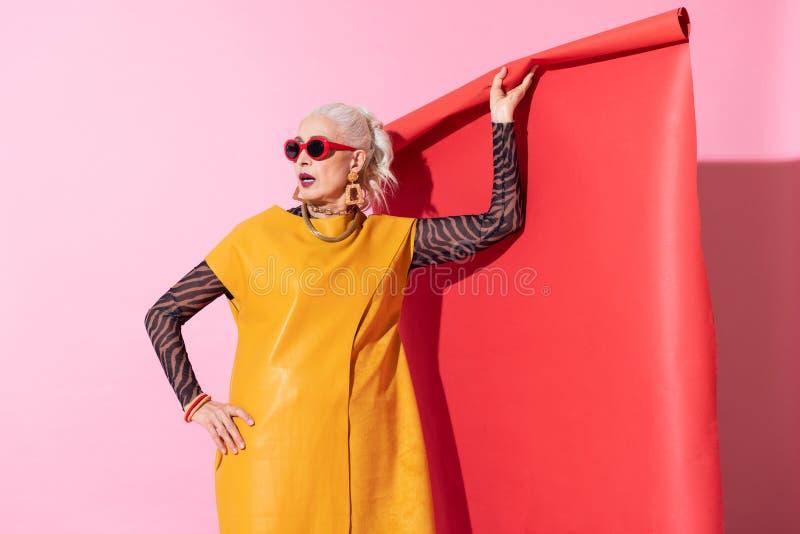 Leuke blonde vrouwelijke status geïsoleerd op roze royalty-vrije stock afbeeldingen