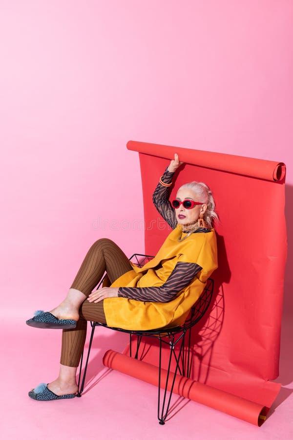 Leuke blonde vrouwelijke zitting op comfortabele stoel royalty-vrije stock fotografie