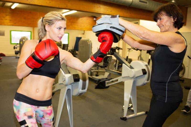 Leuke blondevrouw opleiding met bokshandschoenen bij de gymnastiek met hogere vrouwelijke bus persoonlijke trainer stock foto