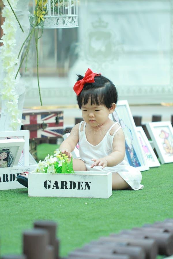 Leuke Chinese het spelbloemen van het babymeisje in een tuin royalty-vrije stock foto's