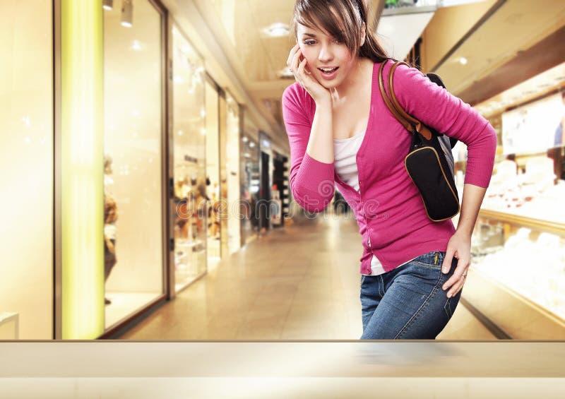 Leuke dame die een winkelvenster bekijkt stock afbeelding