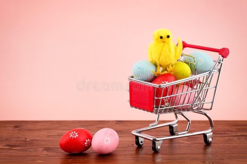 Leuke decoratieve kip op een stapel van kleurrijke geschilderde eieren in een miniboodschappenwagentje op een houten oppervlakte  royalty-vrije stock afbeelding