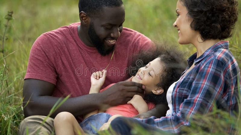 Leuke dochter die in het hoge gras spelen met gevende ouders, houdende van familie liggen royalty-vrije stock afbeelding
