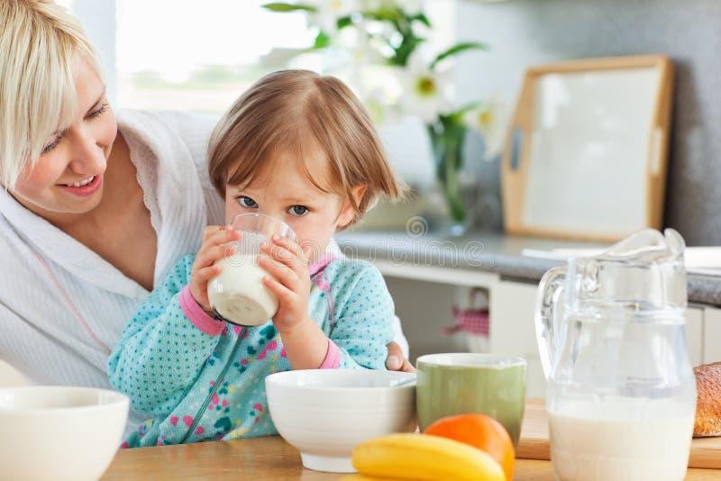 Leuke dochter het drinken melk tijdens ontbijt royalty-vrije stock fotografie