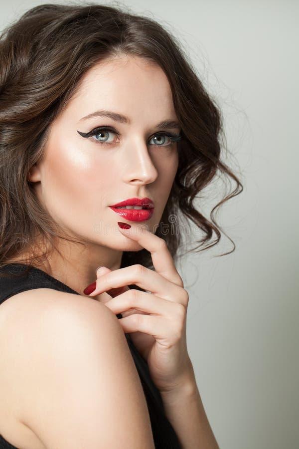 Leuke donkerbruine modelvrouw met make-up en bruin krullend haarportret stock fotografie