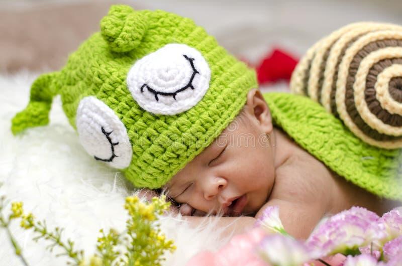 Leuke en aanbiddelijke pasgeboren baby met de slaap van het slakkostuum royalty-vrije stock foto's