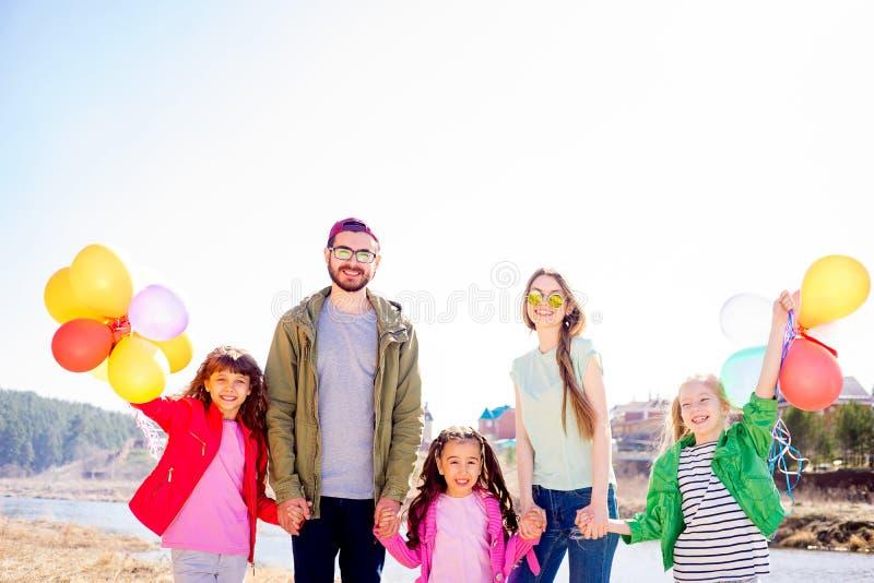 Leuke familie die en ballons lopen houden royalty-vrije stock fotografie