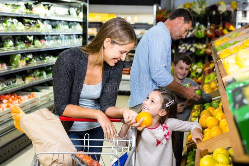Leuke familie die kruidenierswinkels samen kiezen stock foto