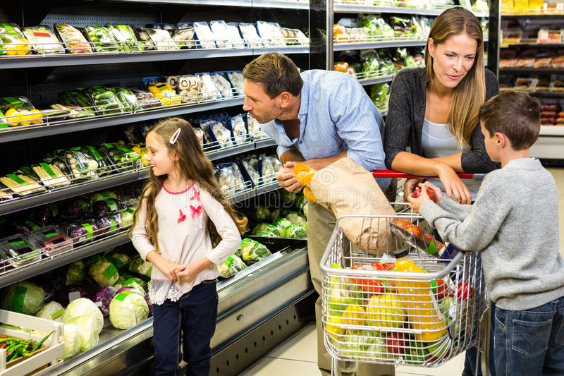 Leuke familie die kruidenierswinkels samen kiezen royalty-vrije stock afbeeldingen