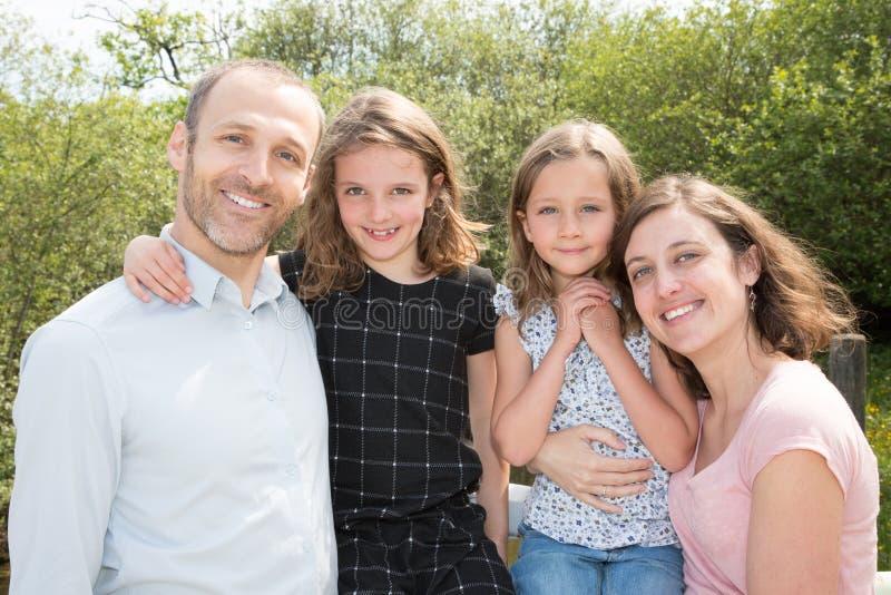 Leuke familie van vier in openlucht met vadermoeder en twee zustersdochters stock fotografie