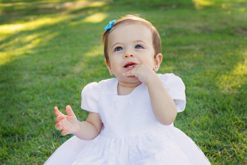 Leuke gelukkig glimlachend weinig babymeisje in witte kledings krassende eerste tanden royalty-vrije stock foto's
