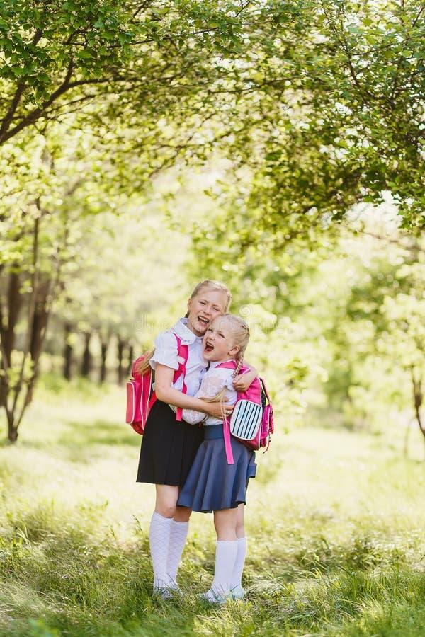 Leuke gelukkige blondemeisjes in school het eenvormige in openlucht koesteren stock foto