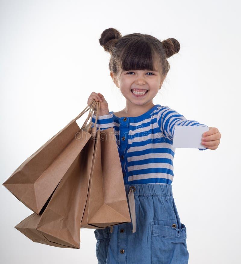 Leuke gelukkige de korting van de kindholding witte kaart en het winkelen zakken in haar handen Jong geitje met creditcard Meisje royalty-vrije stock afbeelding