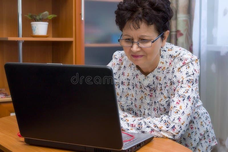 Leuke gelukkige hogere vrouw met oogglazen die met het notitieboekje thuis werken stock foto