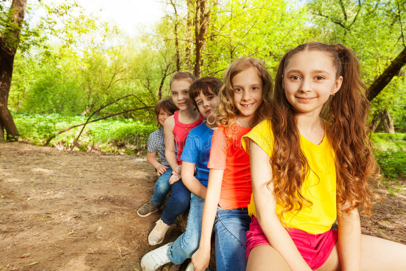 Leuke gelukkige jonge geitjes die op login het bos zitten stock afbeeldingen