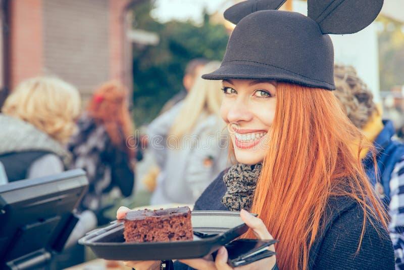 Leuke gelukkige jonge vrouw in een hoed die een cake in openlucht eten royalty-vrije stock afbeeldingen