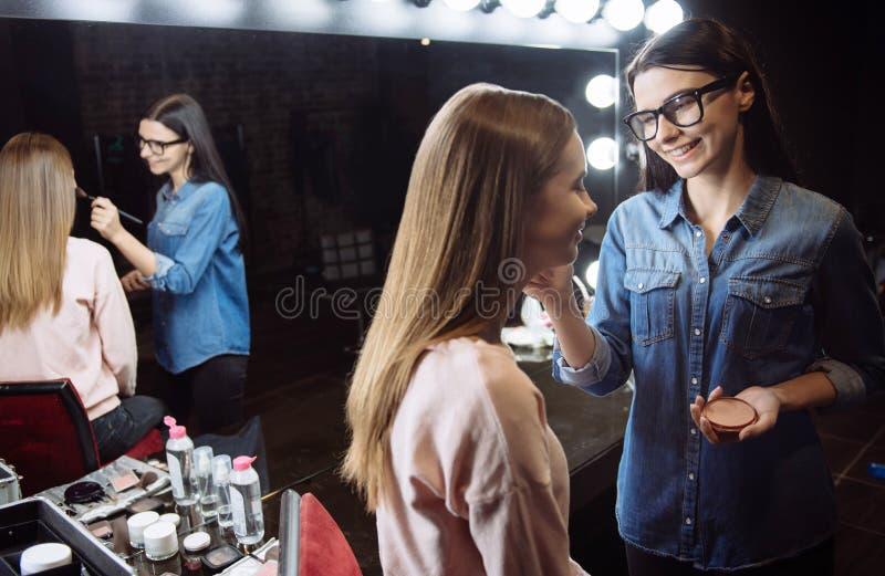 Leuke gelukkige make-upkunstenaar die op kosmetisch poeder zetten stock foto's
