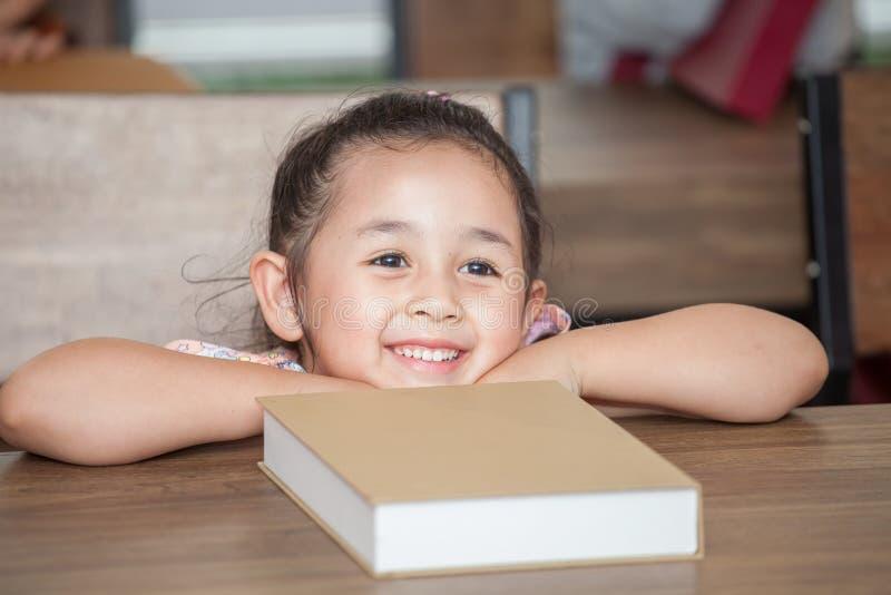 Leuke gelukkige meisjestudent die op lijst met boek in klaslokaal basisschool leunen jong geitje of kind slimme zitting bij burea stock foto