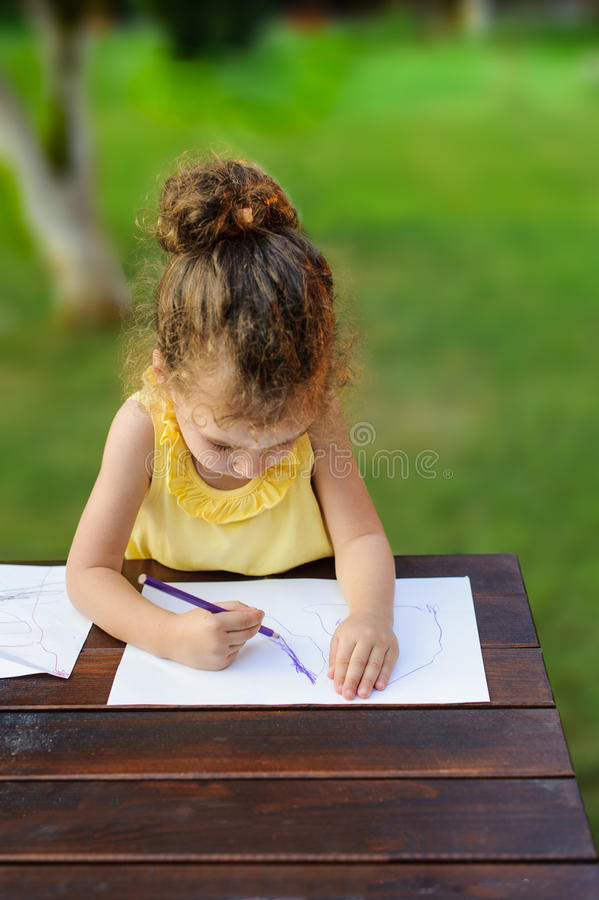 Leuke gelukkige meisjetekening iets in haar notitieboekje bij de tuin royalty-vrije stock afbeeldingen