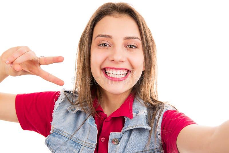 Leuke gelukkige vrouw in denimjasje die twee vingers tonen en bij camera glimlachen royalty-vrije stock fotografie